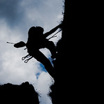 Silhouette of person climbing a mountain
