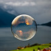 Morning light reflected in a soap bubble over the fjord