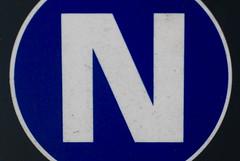 symbol(0.0), number(0.0), house numbering(0.0), circle(0.0), traffic sign(0.0), vehicle registration plate(0.0), brand(0.0), signage(1.0), trademark(1.0), sign(1.0), line(1.0), font(1.0), blue(1.0),