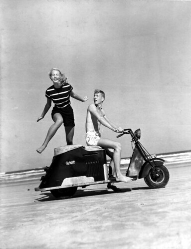Betty Boone jumping over a motor scooter driven by Don Roberson