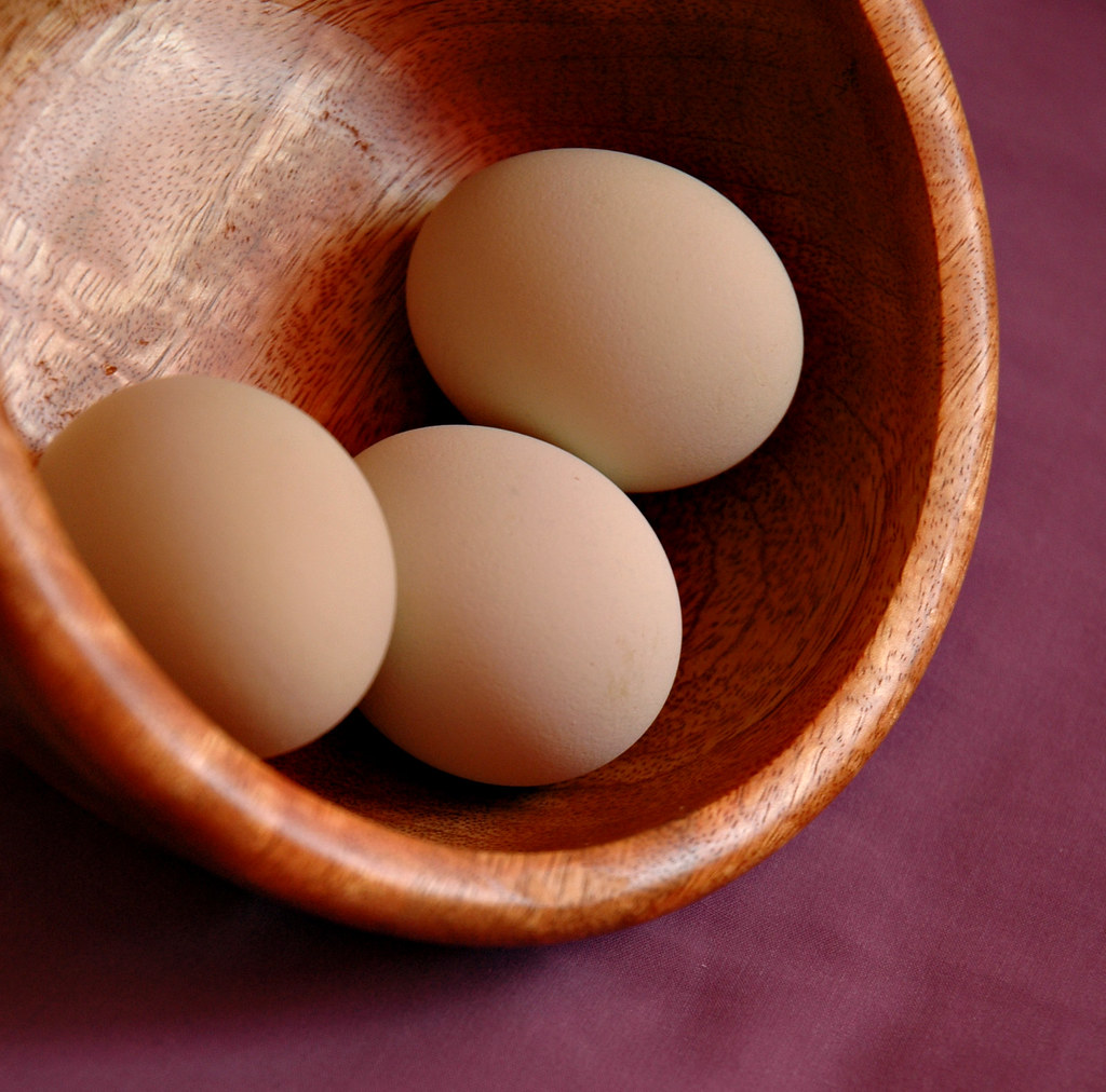 Blue eggs in mango-wood bowl