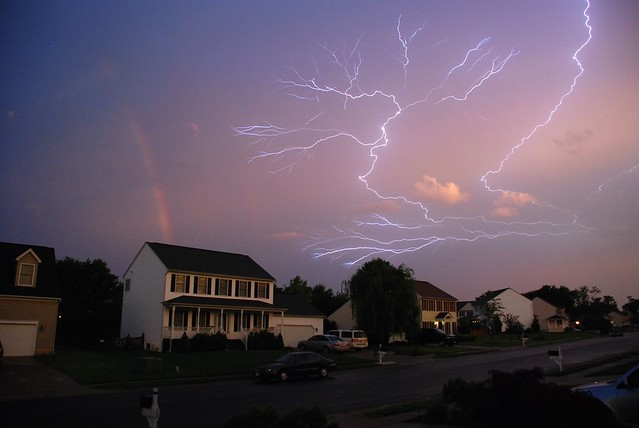 Rainbow with Lightning running through the Clouds at Sunset