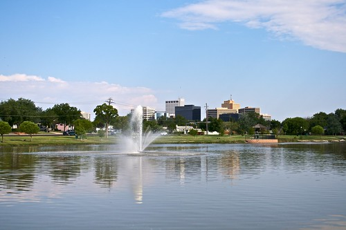blue trees sky green water fountain grass skyline clouds buildings pond tx midland