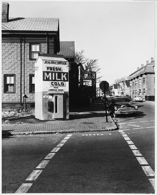 Symbols - Daytime, Milk Carton - Milk Dispenser kiosk, 24 Hour Self-service, Tall, Milk Carton-shaped Vending Kiosk, Harvard Street, Stop Sign, Parked Buick, Cross Walk with