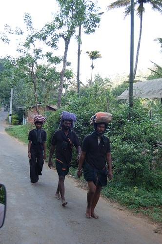drei schwarzgekleidete Männer mit ihren Beuteln auf dem Kopf gehen schweigend auf einer Strasse