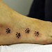 paw prints on foot tattoo