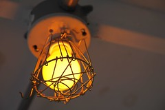 lantern(0.0), lamp(1.0), incandescent light bulb(1.0), light fixture(1.0), yellow(1.0), light(1.0), macro photography(1.0), close-up(1.0), circle(1.0), lighting(1.0),
