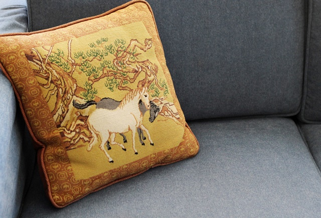 vintage embroidered horses throw pillow on blue couch
