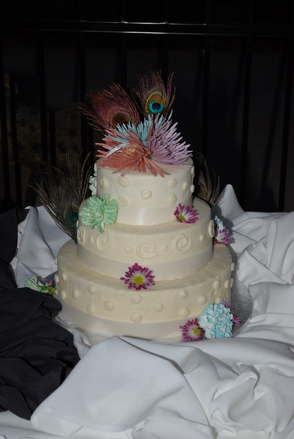 3 tier wedding cake decorated with fresh flowers and peacock feathers