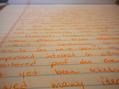 yellow pad paper with orange colored hand writting