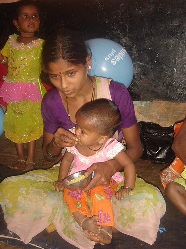 Mother feeding food mixed with Sprinkles Plus to her Baby at Anganwadi center, Karjat, Maharashtra, India