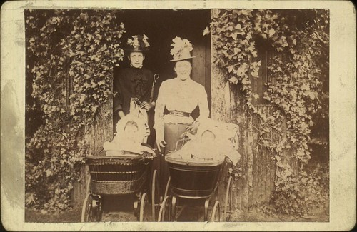 Outdoor posed photograph of two women setting out on a walk with their babies in prams, 1890-1900.