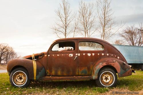 old trees sunset etched broken car metal landscape evening rust automobile dusk rusty weathered decrepit dilapidated corroded junker battered junked runningboard twodoor
