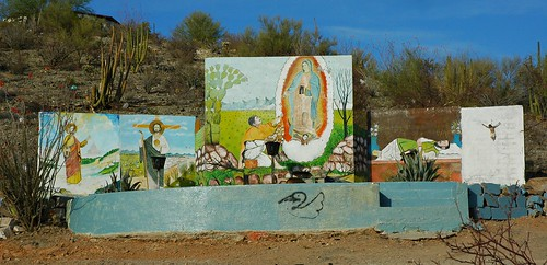 Nuestra Señora de Guadalupe, detailed folk art religious murals, Crucified Christ statue, Hillside shrine, Hermosilla, Mexico by Wonderlane