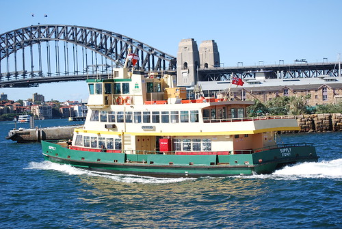 A wooden ferry boat under way heading towards the Harbour Bridge in Sydney's Port Jackson