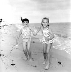 Two friends having fun modeling swimwear at the beach