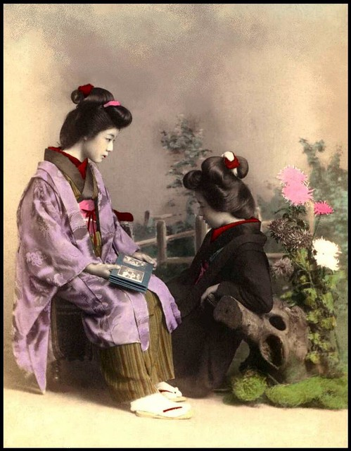 TWO GEISHA SHARING AN ALBUM OF PHOTOGRAPHS