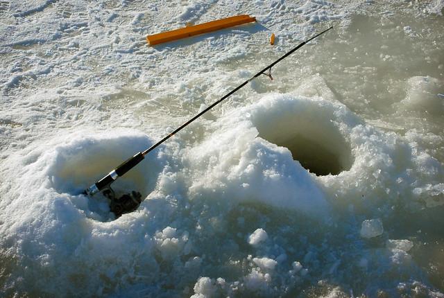Fishing hole an ice rod is set near a fishing hole on for Ice fishing hole