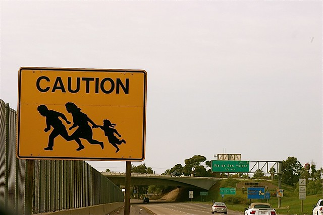 "Photo of a ""Caution"" sign by the side of a highway next to a very tall border wall. The ""Caution"" sign has a picture of a man, woman and child running"