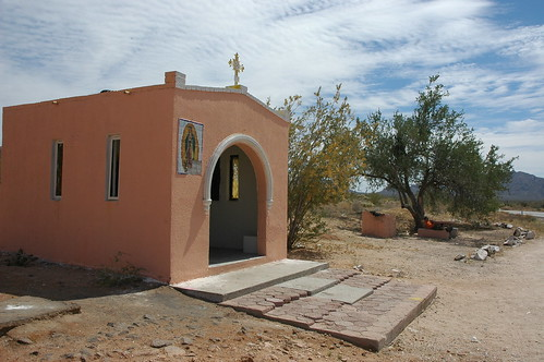Our Lady of Guadalupe, cross, entrance, pink roadside shrine or chapel, a man sits on a concrete tank under a tree, mountains, clouds, Sonora Desert, northern Mexico, along the border, Highway 2 by Wonderlane