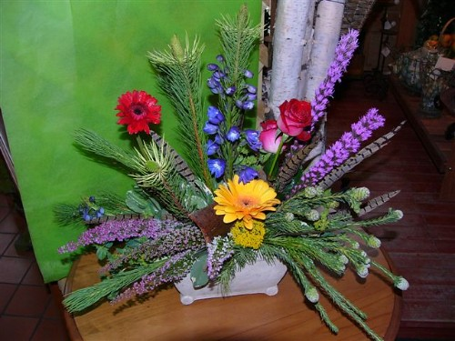 #01ED $75 as shown to $100 Stylized arrangement includes gerbera daisies, liatris, heather, delphinium, roses,  and yarrow.  Faux pheasant feathers are an added touch to this design.
