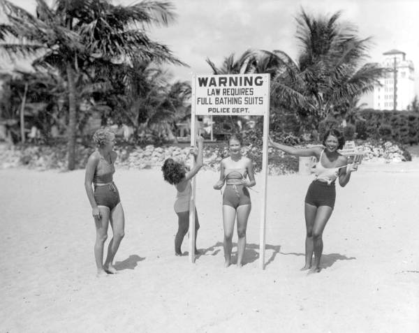 Young women making fun of sign at beach requiring full bathing suits: Miami, Florida
