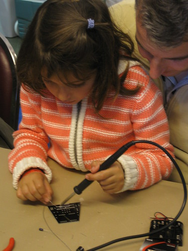 A young girl learning to solder.