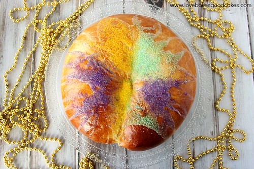 Traditional New Orleans King Cake top view with gold beaded necklaces.