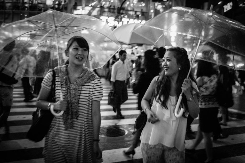 Two girls chatting in the rain with transparent umbrellas.