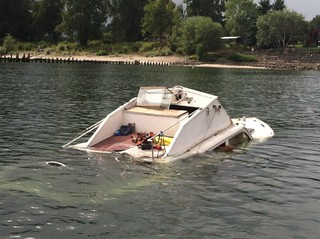 A 26-foot pleasure craft floats partially submerged on the Columbia River north of Portland, Ore., Sept. 16, 2013.  The boat partially sank and then drifted ashore with an unknown amount of fuel on board; Coast Guard Sector Columbia River responders are coordinating the response to minimize any potential pollution to the environment. U.S. Coast Guard photo by Petty Officer Joshua Heldt.