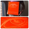 Custom photography book with engraving treatment on orange acrylic