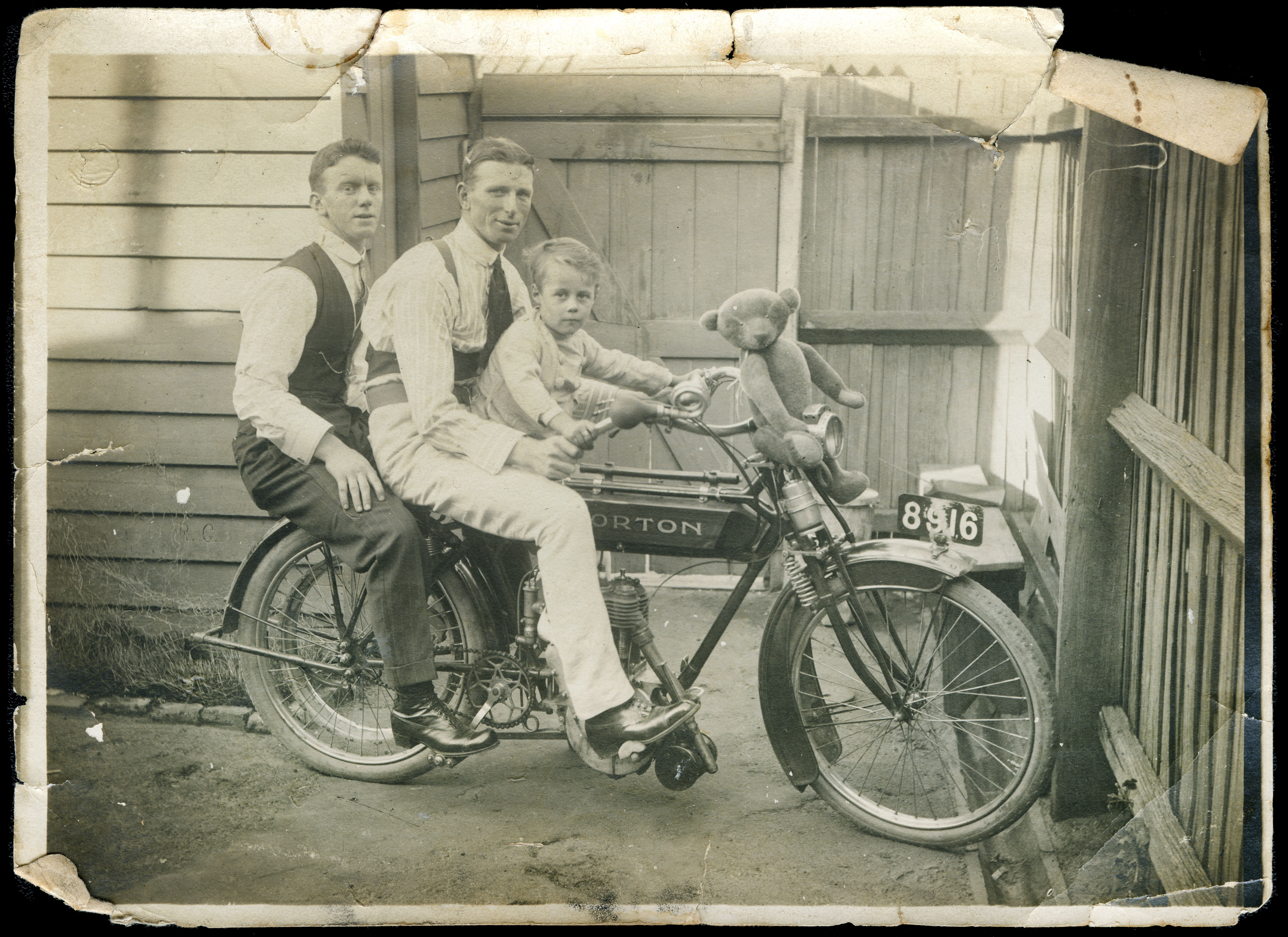 Two men and a young boy (Tom Wild) on a motorbike, with a teddy bear sitting on the handle bars
