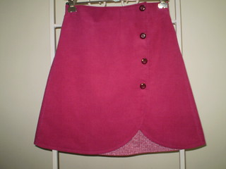 "Clever Charlotte ""chickadee skirt"". Size 6, lengthened by several inches. Pink pinwale corduroy, lined with 'ancient' quilting cotton from stash, and decorated with 4 mulberry coloured ""genuinely retro"" buttons."