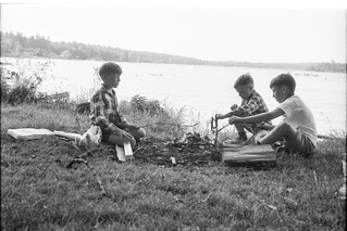 Boys around a campfire by the water.