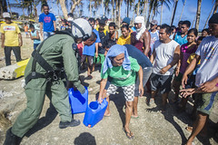 Naval Aircrewman (Tactical Helicopter) 2nd Class Jason Rimando passes water containers to local residents in Henane Nov. 16 during Operation Damayan. (U.S. Navy photo by Mass Communication Specialist 3rd Class Paolo Bayas)