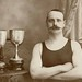 Man in a swimming costume standing with two trophies by Australian National Maritime Museum on The Commons