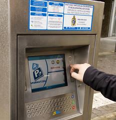 Una persona recoge su ticket en uno de los expendedores