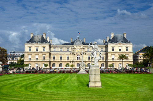 Jardin du Luxembourg with the Palace and statue. Few flowers are in front and blue sky behind, Paris, France