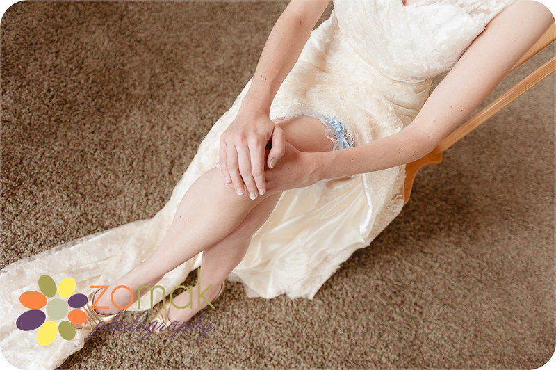 The bride calmly awaits her wedding ceremony and shows off her garter in the meantime.