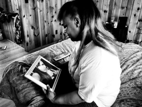 "A black and white photo of Lyniece Nelson gazing at a picture of her daughter, Shellye ""Treasure"" Hilliard."