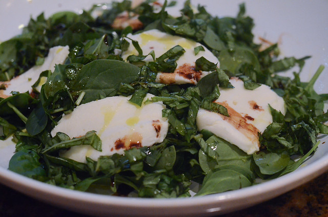 A bowl with spinach, basil, balsamic vinaigrette and mozzarella.