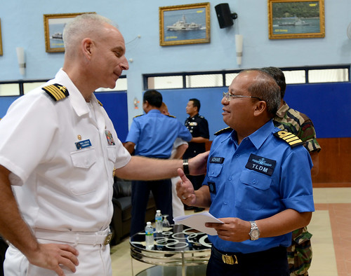 Capt. Paul Schlise, Commander, Destroyer Squadron 7, speaks with a member of the Royal Malaysian Navy