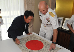 Rear Adm. James F. Caldwell points out inscriptions to Consul General of Japan Toyoei Shigeeda following a brief ceremony at the Consulate-General of Japan in Honolulu July 26 to return the flag Caldwell's great uncle received during WWII. (U.S. Navy Photo by Mass Communication Specialist 2nd Class David Kolmel)