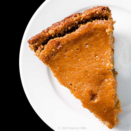 Sweet Potato Pie on white plate, overhead view on black