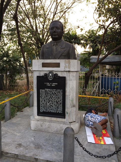Quirino statue and sleeping homeless person