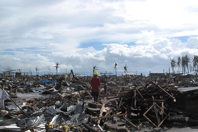 A man stands surrounded by the devastation wrought by Typhoon Haiyan in the city of Tacloban from Flickr via Wylio