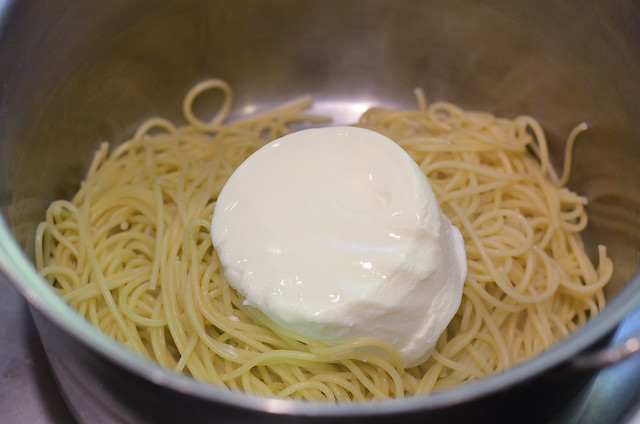 Ricotta cheese is added to cooked spaghetti.