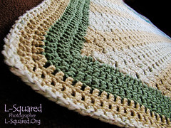 Blanket made of diagonal beige and white stripes with a green, beige and white edging.