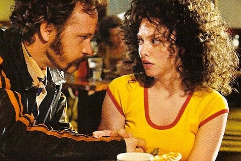 A dude with  a gross mustache leans over Amanda Seyfried in Lovelace