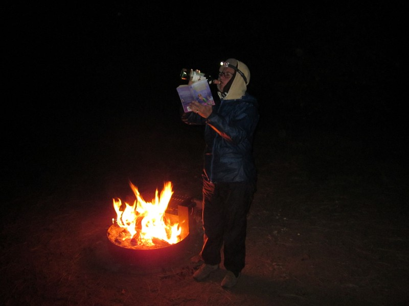 Car Camping - drinking wine while reading a book by headlamp at the campfire